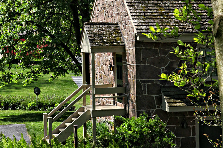 The front exterior of Covered Bridge cottage with beautiful greenery surrounding.