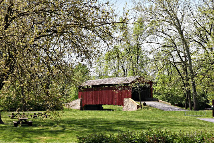 A covered bridge can be seen from one of the many views out a bedroom window.