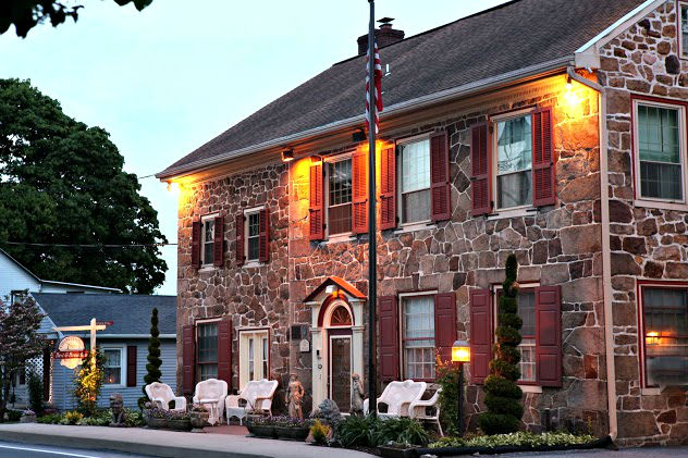 A front view of the Inn with warm lights and a comfortable seating area.
