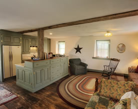 View of cottage kitchen with light green wooden cabinets and sitting area with a multi colored oval rug.