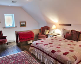 Cabin bedroom with red an white block patterned bedding.