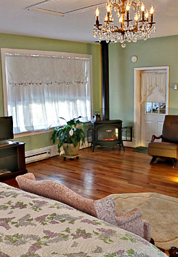 First floor bedroom showing a large sitting area with a warming gas stove and light green theme.
