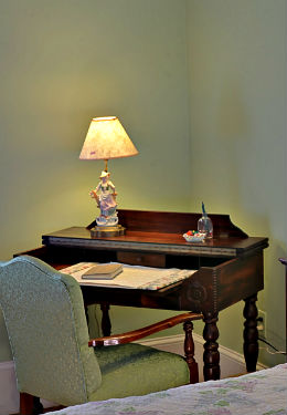 A cosy writing desk next to the queen bed with gentle lighting and subtle green background.