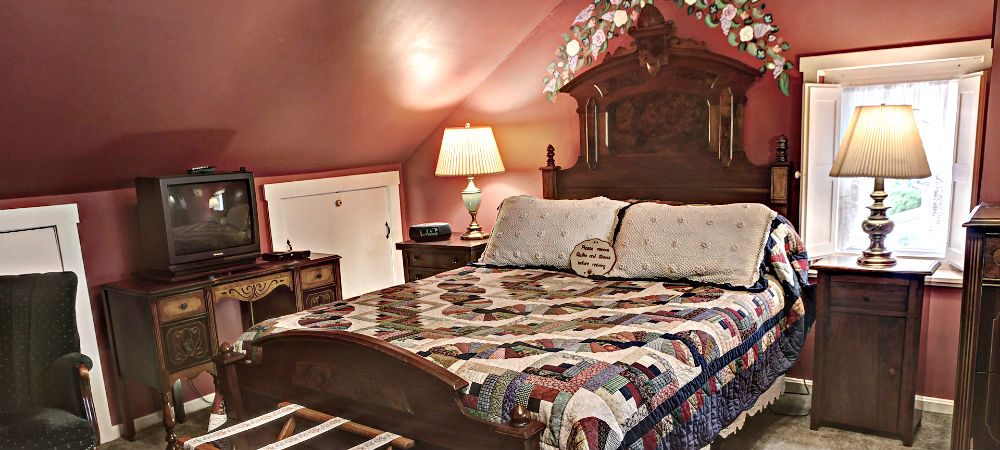 The mauve-themed Fausset room queen bed with an ornate headboard.
