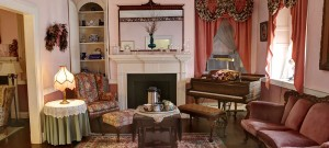 Tea Parlor Room decorated in shades of rose with green accents, a tea set sitting in front of a white wood framed fireplace