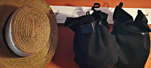 Tan and black Amish hats hanging on a simple rack.