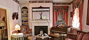 Sitting room with piano and fireplace decorated in pink hues and accented with floral fabrics and wallpaper border