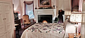 The second floor beautifully furnished Davies room with a warm fire and a light pink theme.